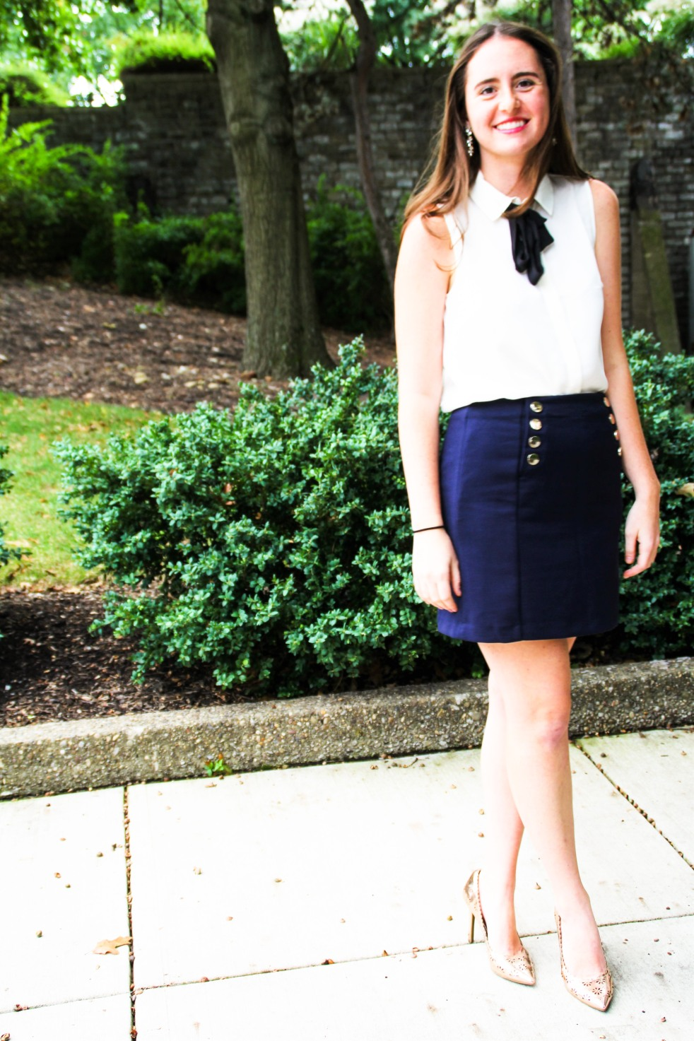 preppy outfit style navy button skirt h&m tie neck bow blouse statement earrings rose gold heels outfit of the day